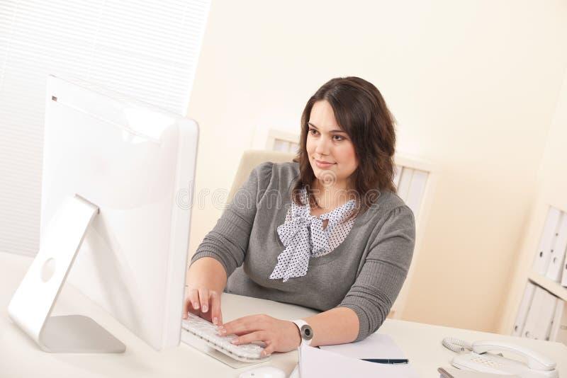 Junge attraktive Geschäftsfrau, die im Büro arbeitet lizenzfreies stockbild