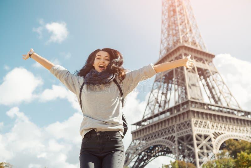 Junge attraktive glückliche Frau, die für Freude gegen Eiffelturm in Paris, Frankreich springt lizenzfreie stockbilder