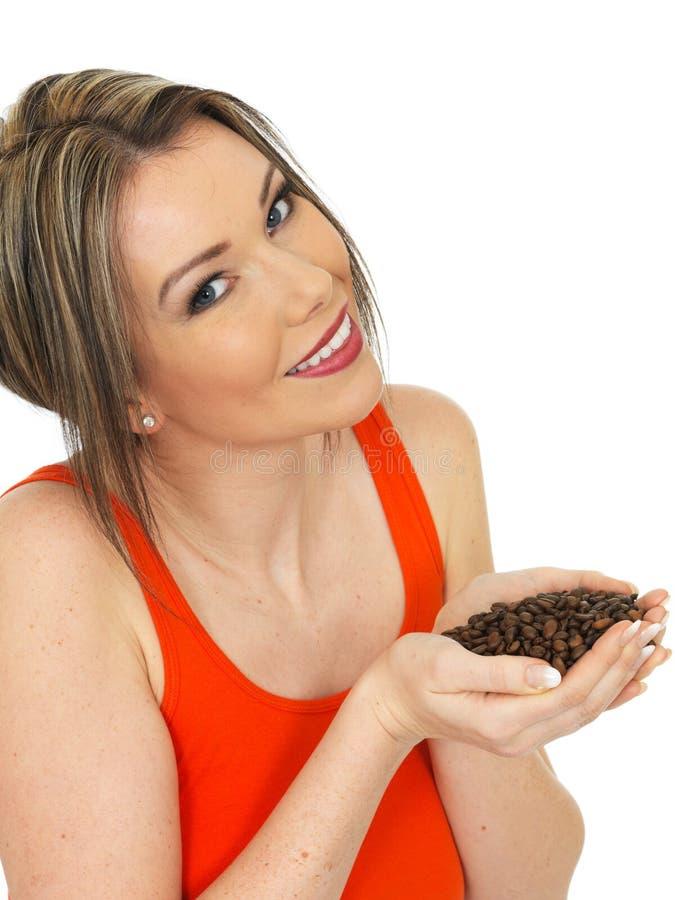 Junge attraktive glückliche Frau, die frische Braten-Kaffeebohnen hält stockbild