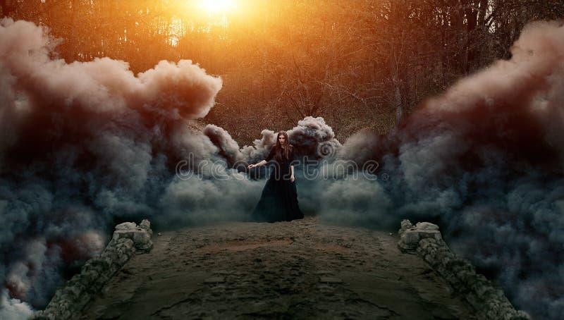 Junge attraktive Hexe, die auf die Brücke im schweren schwarzen Rauche geht stockbild