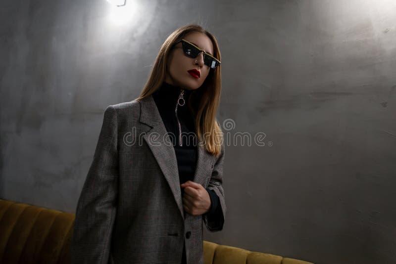 Junge attraktive Hippie-Frau in den ungewöhnlichen stilvollen Gläsern in einer eleganten karierten Jacke der Weinlese in einem sc stockbild