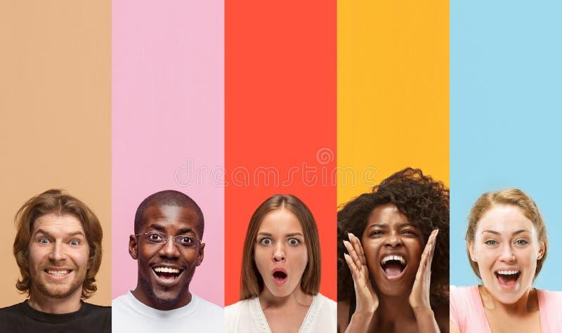 Junge attraktive Leute, die auf mehrfarbigem Hintergrund erstaunt schauen stockbild