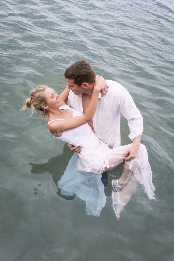 Junge attraktive Paare, die im Wasserbecken flirten stockbild