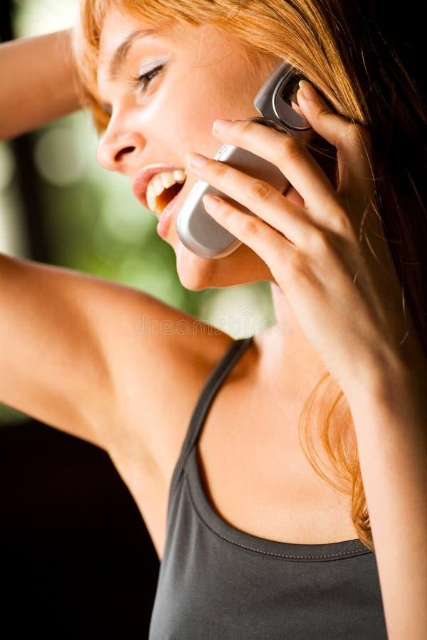 Junge attraktive red-haired lächelnde Frau am Telefon, draußen stockbild
