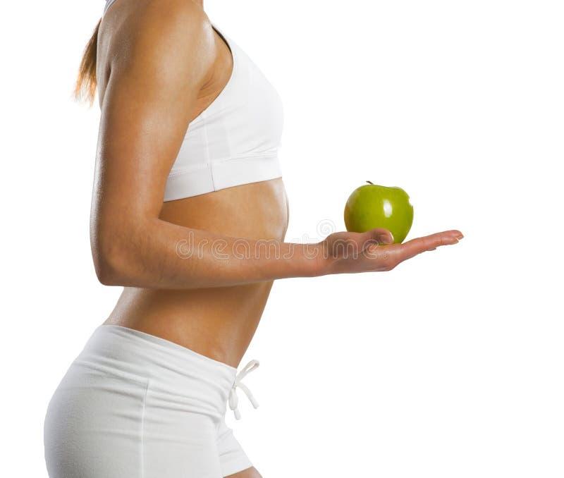 Junge attraktive sportliche Frau mit grünem Apfel lizenzfreies stockfoto