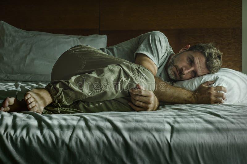 Junge attraktive traurige und depressive Menschen weinen hilflos auf dem Bett zu Hause Schlafzimmer und fühlen sich überwältigt u stockbild
