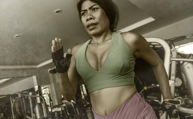 Junge attraktive und athletische asiatische indonesische Sportfrau, die auf Tretmühle am harten rüttelnden Training des Turnhalle stockbilder