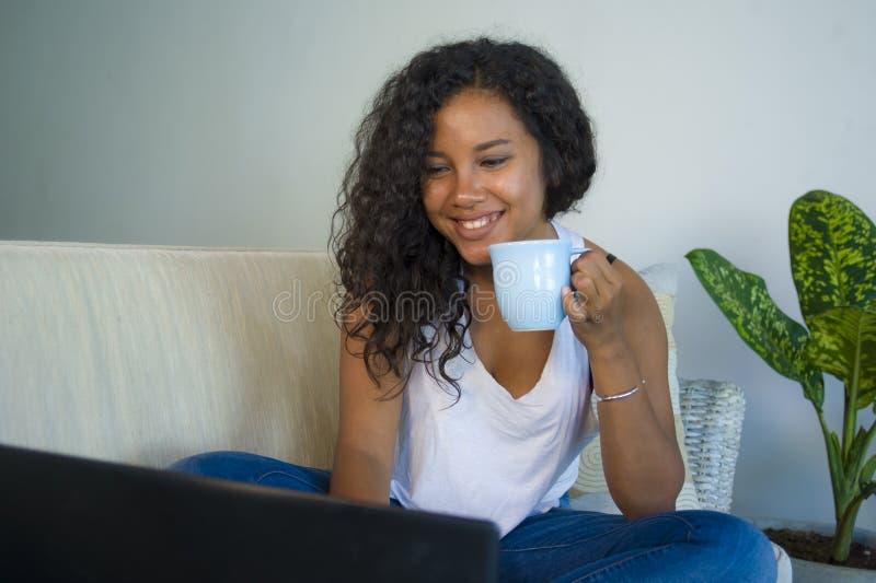 Junge attraktive und entspannte hispanische Studentenfrau, die zu Hause Sofacouchvernetzung mit Laptop-Computer trinkendem Kaffee lizenzfreies stockbild