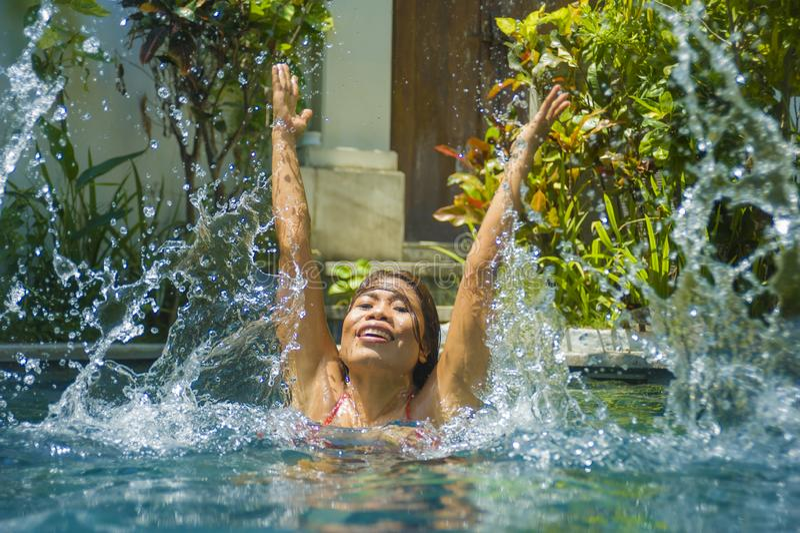 Junge attraktive und glückliche Asiatin im Bikini, der im Swimmingpoolspritzwasser nett spielt, Spaß habend Sommer genießend stockfotografie
