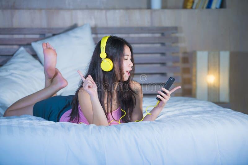 Junge attraktive und glückliche asiatische Chinesin mit gelben Kopfhörern zu Hause hörend Musik im Handy auf Bett lächelndes ha stockbilder