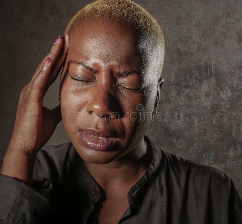 Junge attraktive und traurige schwarze afroe-amerikanisch Frau mit den Fingern auf ihrem leidenden Kopfschmerzen- und Migränegefü lizenzfreies stockfoto
