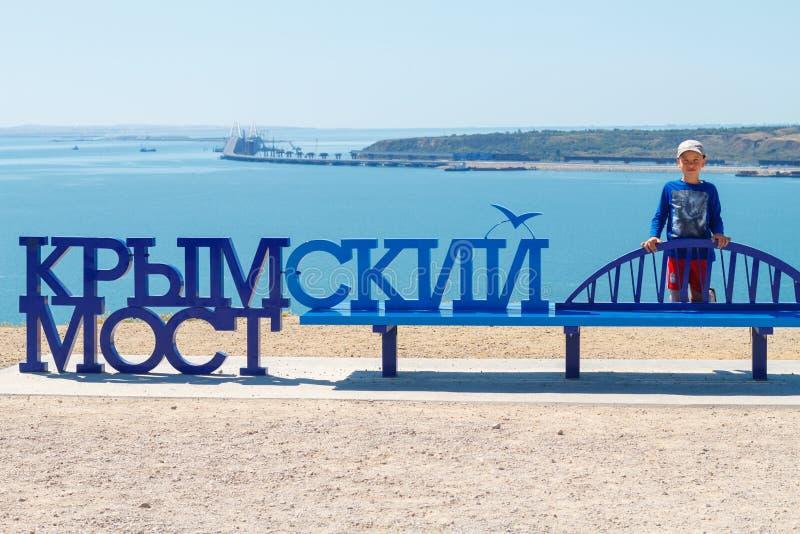 Junge auf dem Hintergrund des Meeres nahe der Aufschriftkrimbrücke lizenzfreies stockfoto
