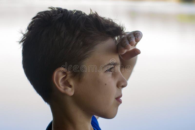 Junge auf dem Riverbank lizenzfreie stockfotografie