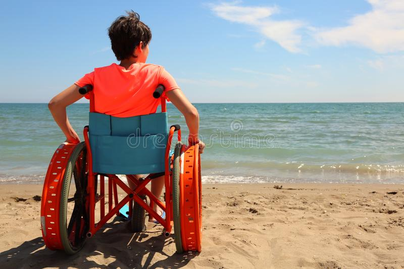 Junge auf dem Rollstuhl durch das Meer lizenzfreies stockfoto
