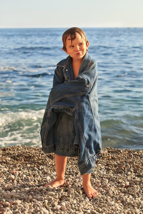 Junge auf dem Strand trägt Vati ` s Jacke lizenzfreie stockbilder