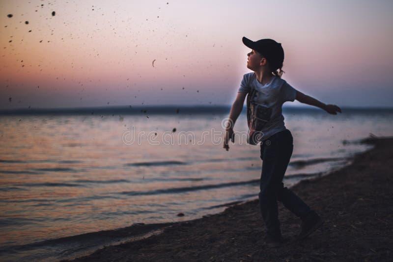 Junge auf dem Strand wirft Steine in das Wasser lizenzfreies stockbild