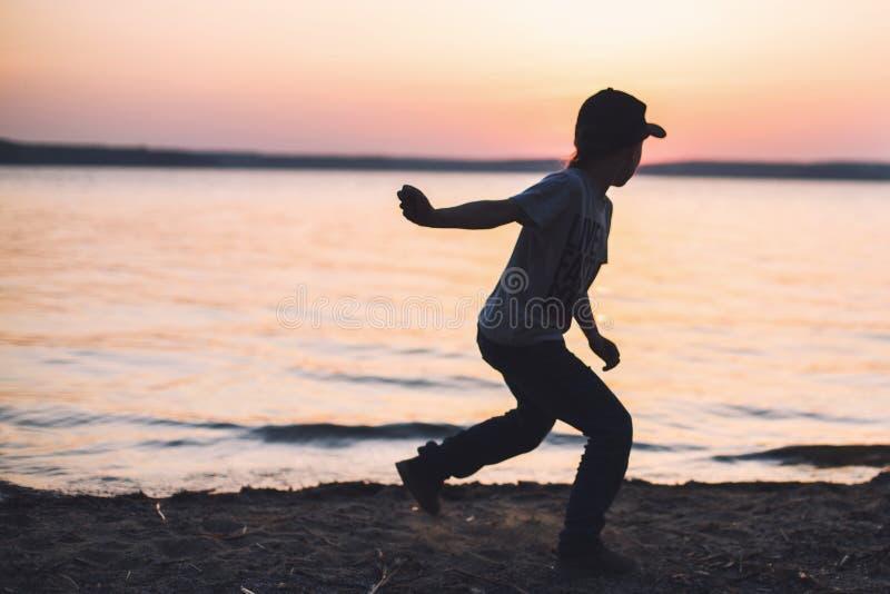 Junge auf dem Strand wirft Steine in das Wasser lizenzfreie stockfotografie