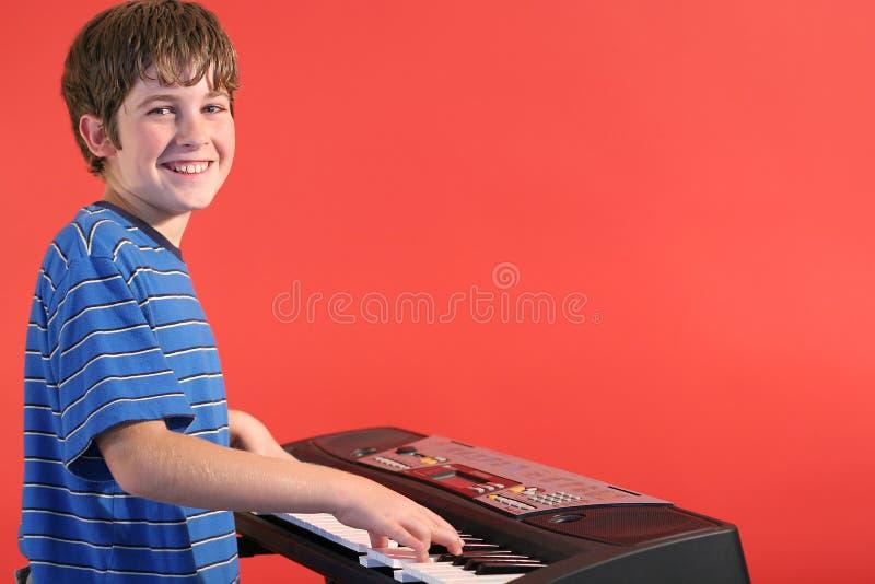 Junge auf der Tastatur gelassen lizenzfreies stockbild