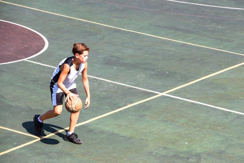 Junge auf einem Basketballplatz stockfoto