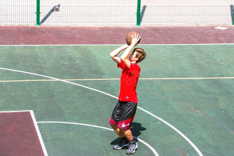 Junge auf einem Basketballplatz lizenzfreie stockbilder