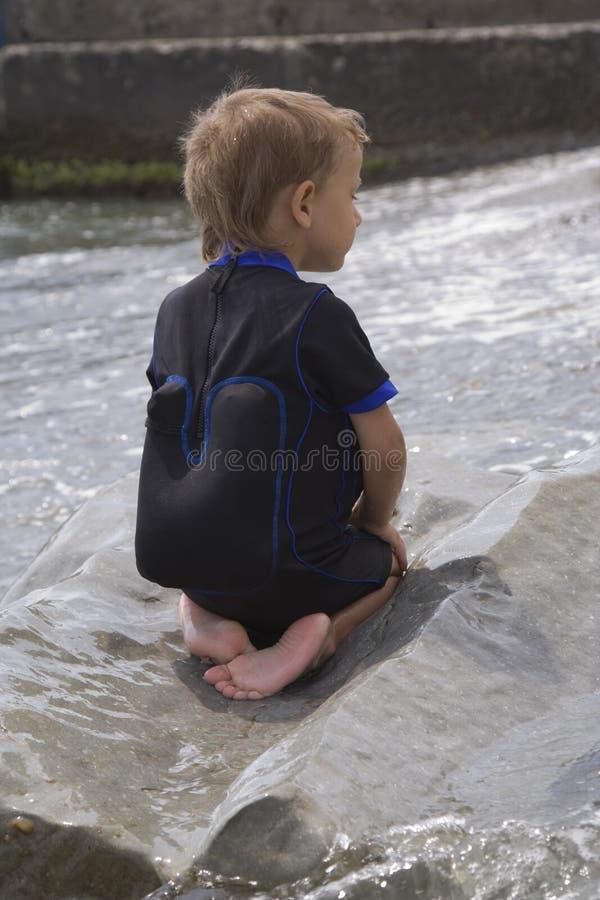 Junge auf einem großen nassen Stein lizenzfreies stockfoto
