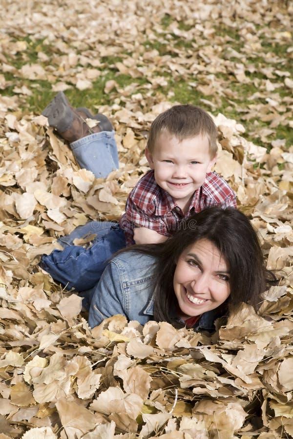 Junge auf Mammarückseite in den Blättern stockfotos