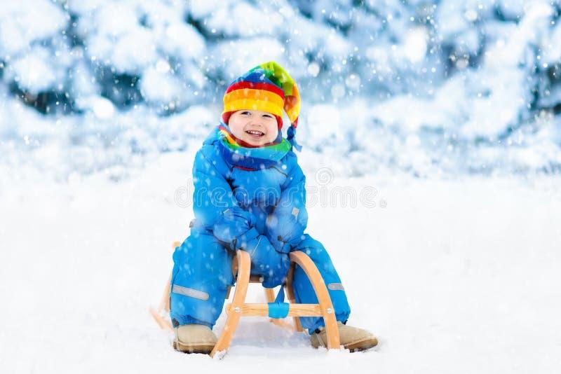 Junge auf Pferdeschlittenfahrt Kinderrodeln Kind mit Schlitten stockfoto