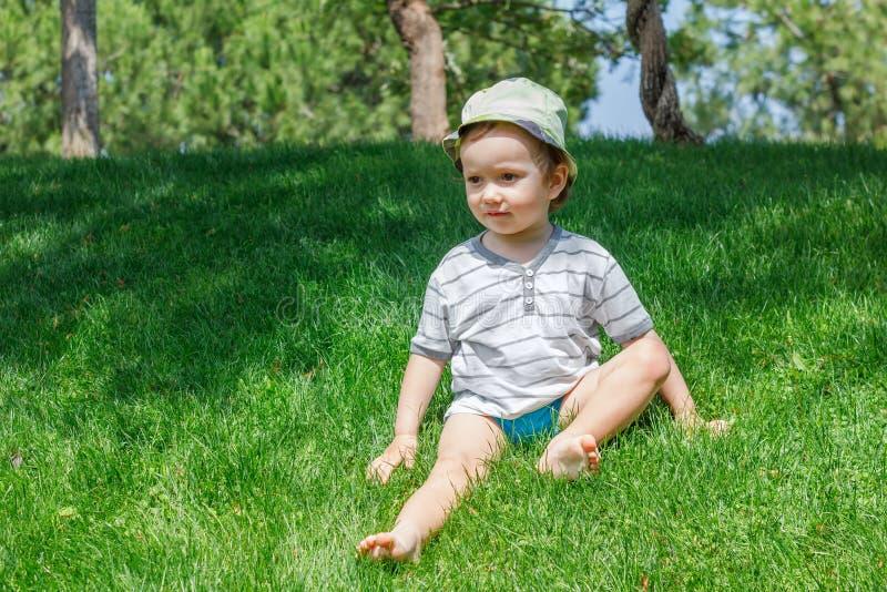 Junge auf Rasen des grünen Grases im Sommerpark, nett lizenzfreie stockfotografie