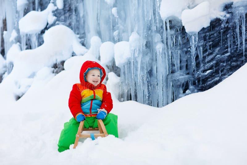 Junge auf Schlittenfahrt Kinderrodeln Kind auf Schlitten stockfotos