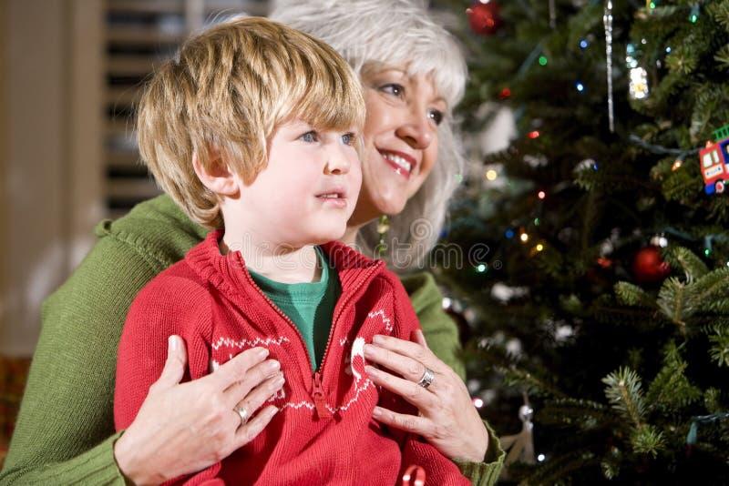 Junge auf Schoss der Großmutter durch Weihnachtsbaum stockfoto