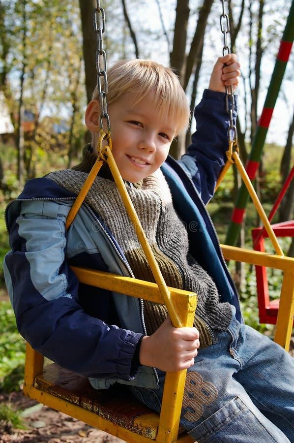 Junge auf Schwingen lizenzfreies stockbild