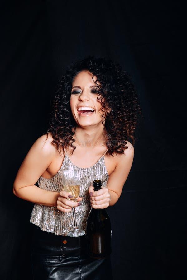Junge ausdrucksvolle Frau auf dem trinkenden Champagner des schwarzen Hintergrundes, neues Jahr feiernd lizenzfreie stockfotos