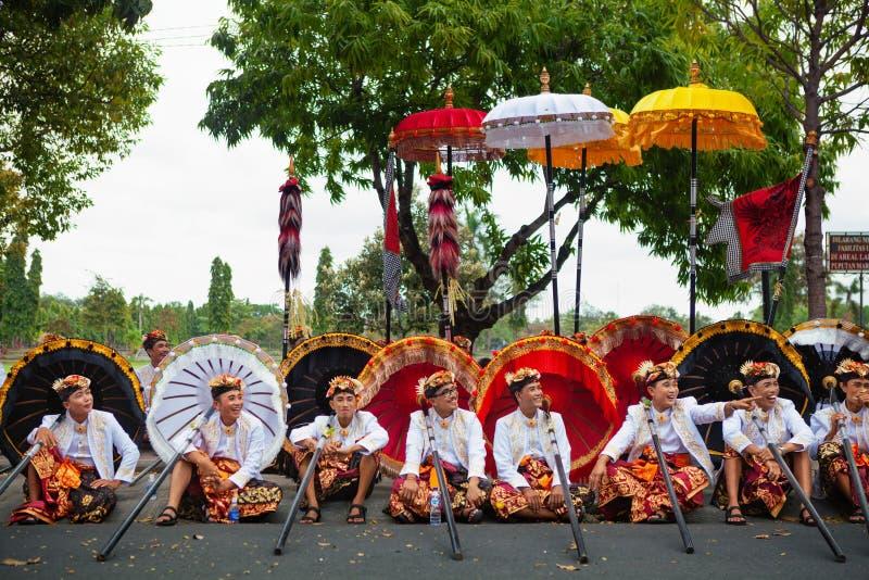 Junge Balinesemänner in den ethnischen Kostümen mit traditionellen Regenschirmen lizenzfreie stockfotografie