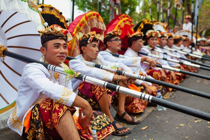 Junge Balinesemänner in den ethnischen Kostümen mit traditionellen Regenschirmen lizenzfreie stockbilder