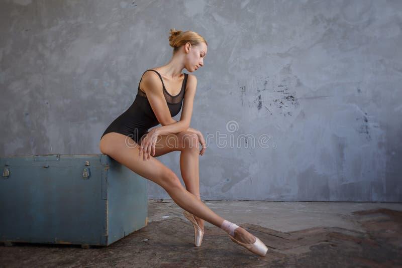Junge Ballerina in einem schwarzen Tanzenanzug wirft in einem Dachbodenstudio auf lizenzfreie stockbilder