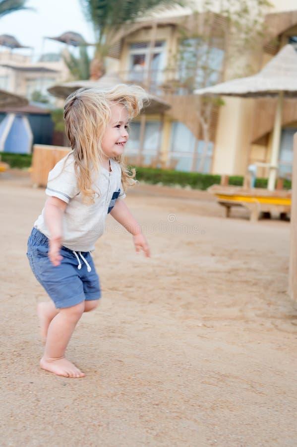 Junge barfuß laufen gelassen auf Sand stockbilder