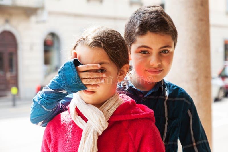 Junge bedeckt Augen seiner Schwester, Porträt stockfotos