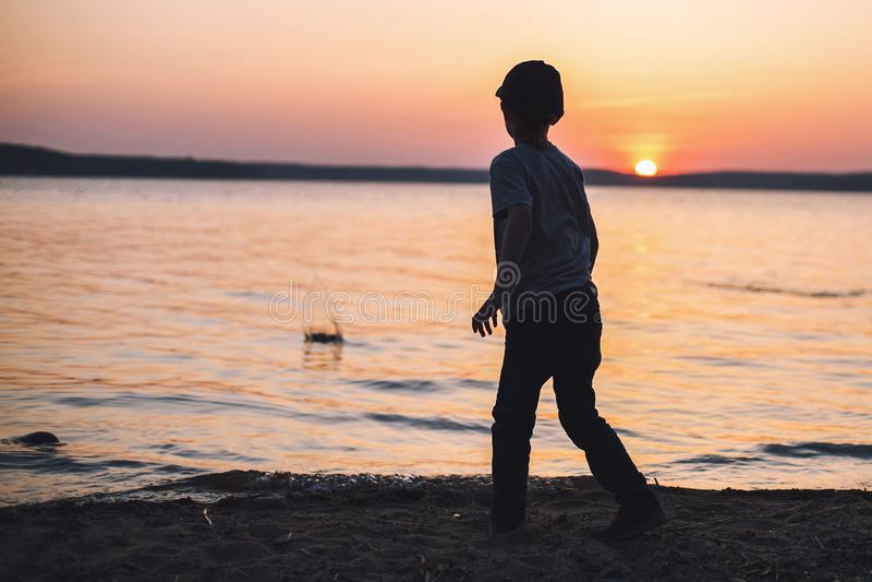 Junge bei Sonnenuntergang auf den Strandwurfssteinen stockfotografie