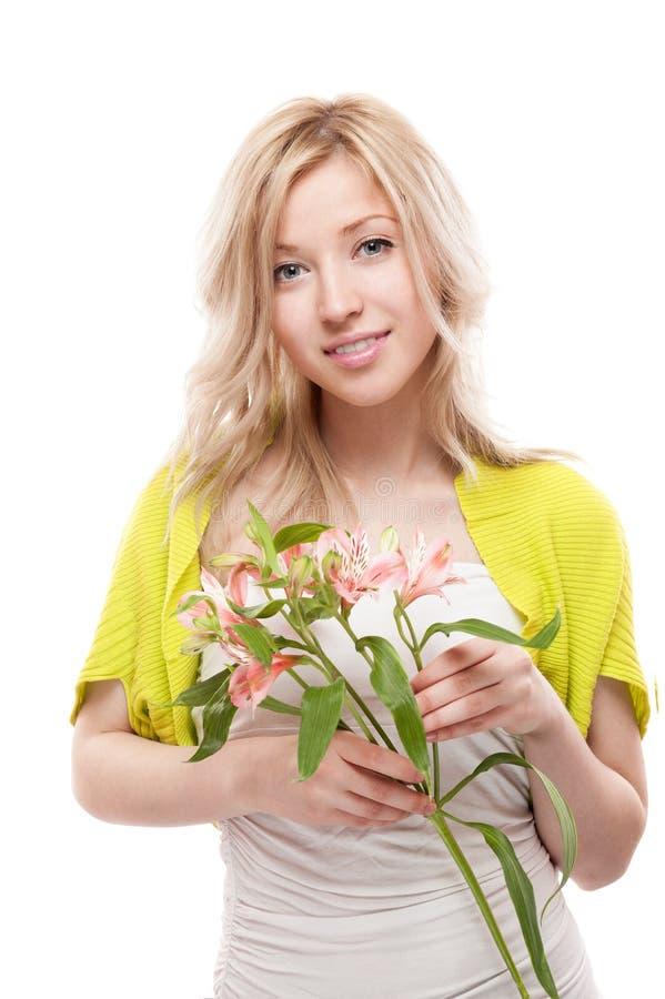 Junge beiläufige lächelnde blonde Frauenholdingblumen stockbild