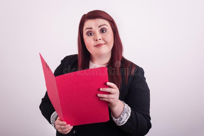 Junge Berufsfrau, die offen einen roten Dateiordner halten zeigt auf ihn ist stockbild