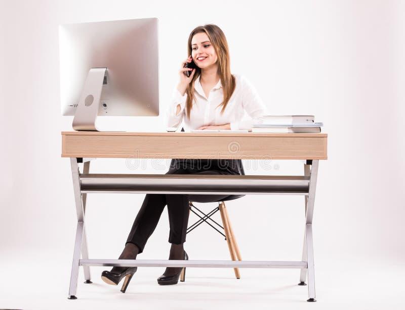 Junge Berufsgeschäftsfrau, die an ihrem Schreibtisch spricht am Telefon auf weißem Hintergrund arbeitet stockfotos