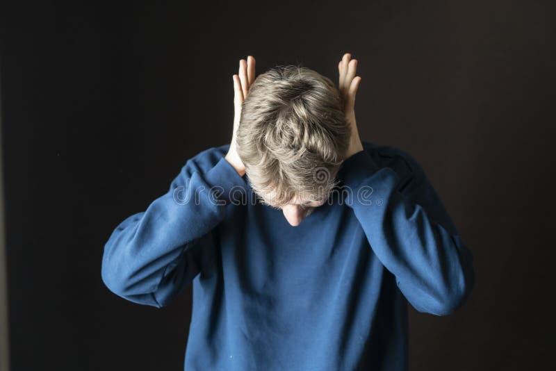 Junge betonten den Mann, der seine Ohren vor lauten irritative Geräuschen f schützt lizenzfreies stockbild