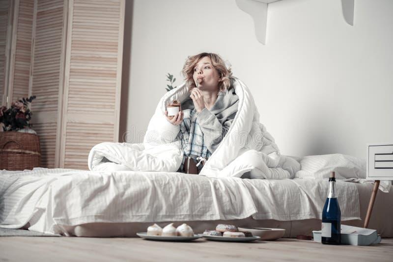 Junge betonten die Frau, die Bonbons isst und Alkohol im Bett trinkt lizenzfreies stockfoto