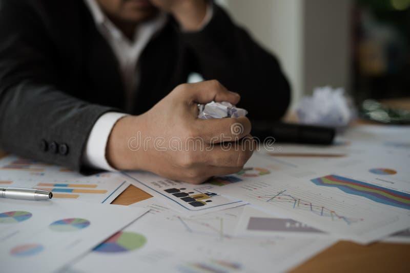 Junge betonten die Geschäftsmannhand, die ein Papier auf seinem Schreibtisch a erfasst lizenzfreie stockbilder