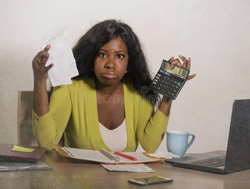 Junge betonten und überwältigten Schwarzafrikaner Amerikanerin, die inländische Buchhaltung mit dem Taschenrechner tut, der umgek stockfoto