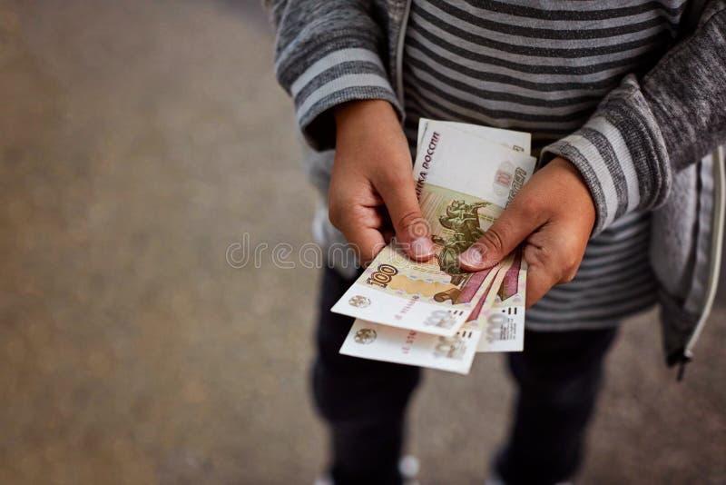 Junge betrachtet russisches Geld, Anmerkungen über 100 Rubel lizenzfreie stockbilder
