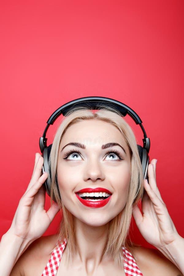 Junge blond-haarige Frau mit Kopfhörern lizenzfreies stockfoto