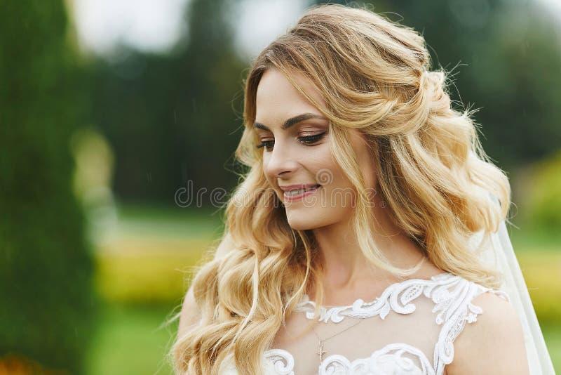 Junge blonde Braut mit einem schönen Lächeln und mit stilvoller Heiratsfrisur im weißen Freien der Spitzes Kleidermorgens stockbild