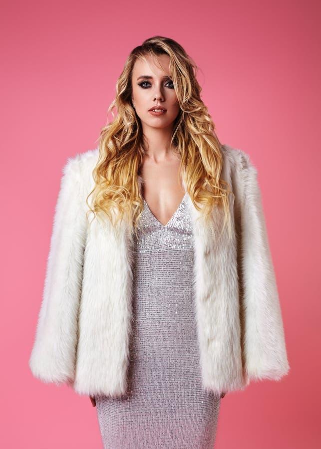 Junge blonde Dame kleiden in Mode, Pelz-Mantel an Sexy Frau, die auf rosa Hintergrund in der modernen Luxuskleidung, Schuhe aufwi stockfotos