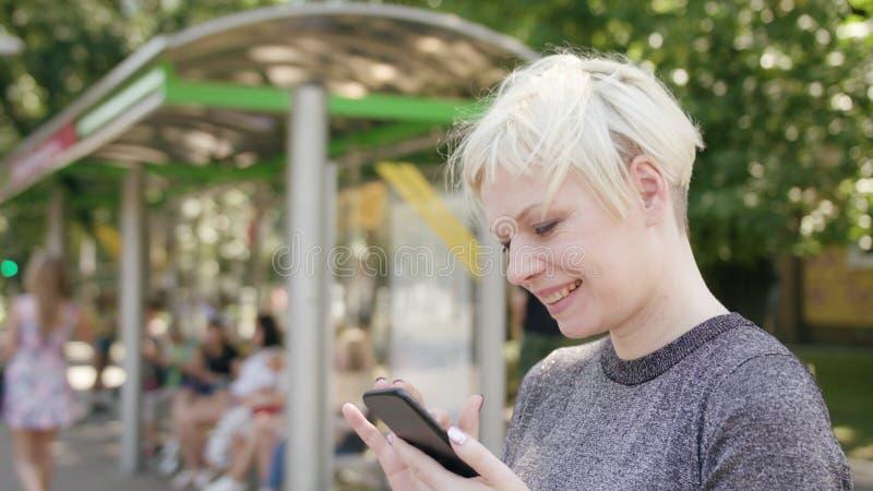 Junge blonde Dame Using ein Telefon in der Stadt stockbilder